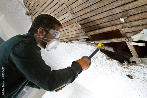 man removing plaster lathe from ceiling with a crowbar.