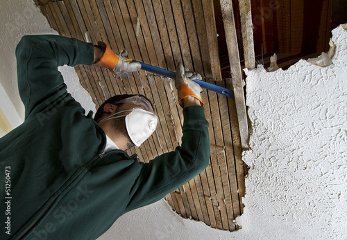a man pulling down plaster ceiling lathe with a crowbar