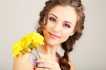 Young woman with beautiful hairstyle and flowers,