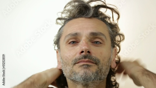 man combing his hair over white