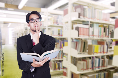 Businessman contemplating at library