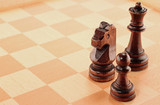 Three Wooden Chess Pieces on a Chessboard