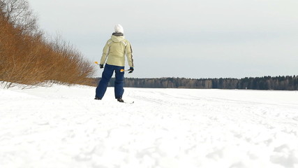girl (person) goes on skis on the snow road in the wood