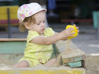 Маленькая девочка играет в песочнице