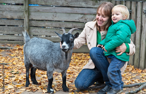 family touching goat in Zoo