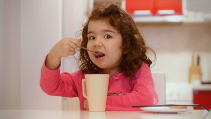 Cute girl learning to eat with spoon and talking to camera