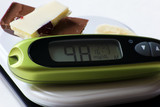 chocolate and glucometer on white background