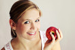 beauty portrait of a young happy woman eating an apple