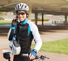 Young Male Cyclist Talking On Cell Phone