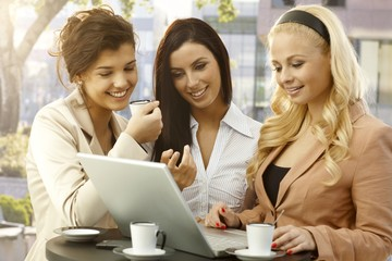 Pretty businesswomen using laptop outdoors