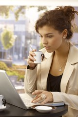 Young businesswoman with laptop and coffee