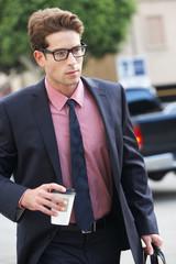 Businessman Hurrying Along Street Holding Takeaway Coffee