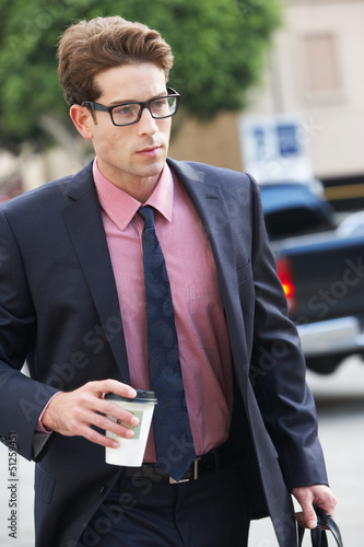 Businessman Hurrying Along Street Holding Takeaway Coffee