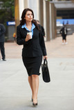 Businesswoman Walking Along Street Holding Takeaway Coffee