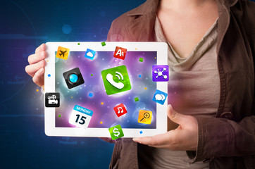 Lady holding a tablet with modern colorful apps and icons