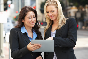 Two Businesswomen Using Digital Tablet Outside Office