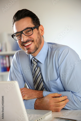 Cheerful businessman working on laptop computer
