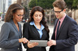 Businessman And Businesswomen Using Digital Tablet Outside