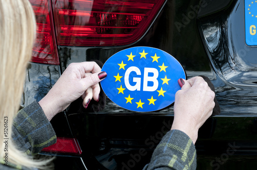 Motorist attaching GB sticker to car