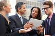 Businessmen And Businesswomen Using Digital Tablet Outside