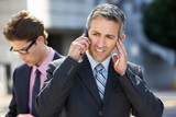 Businessman Speaking On Mobile Phone In Noisy Surroundings