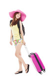 young woman styled in summer outfit  with travel case