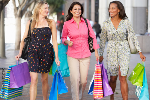 Group Of Women Carrying Shopping Bags On City Street