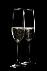 Two glasses of sparkling champagne infront of black