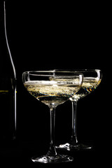 Two glasses of sparkling champagne infront of black background