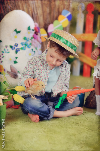 sits a wonderful boy in a straw hat with a chicken and carrots