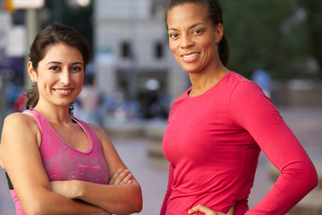 Portrait Of Two Female Runners On Urban Street
