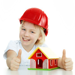 Little girl with helmet shows thumbs up for building a house