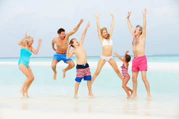 Multi Generation Family Having Fun In Sea On Beach Holiday
