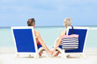 Senior Couple On Beach Relaxing In Chairs