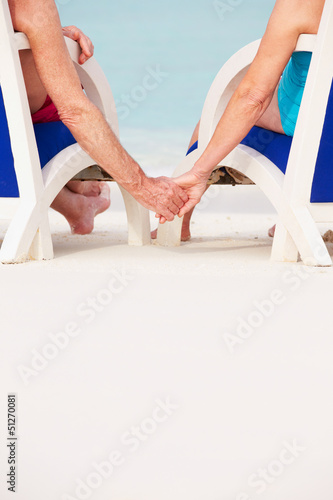 Close Up Of Senior Couple Holding Hands Beach In Chairs