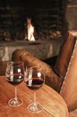 Two Glasses Of Red Wine At A Cosy Fireplace