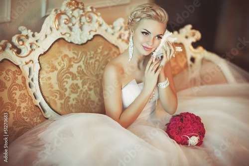 Beautiful bride in wedding dress at home