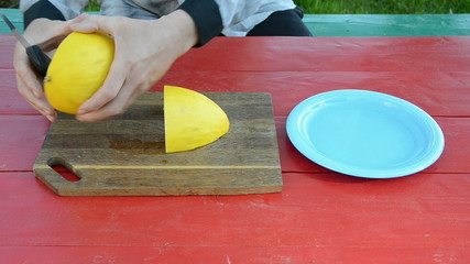 cutting yellow melon on table