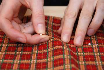 Closeup of two hands pinning red plaid fabric