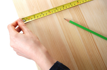Using a steel tape measure on a wooden board against a white bac