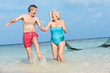 Senior Couple Splashing In Beautiful Tropical Sea