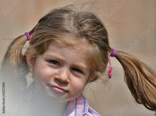 An extremely cute little girl with pigtails.