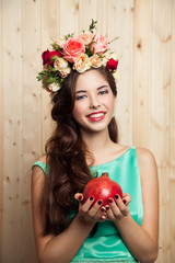 Smiling girl in mint dress with flower crown and pomegranat
