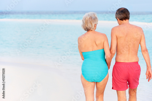 Rear View Of Senior Romantic Couple Walking In Tropical Sea