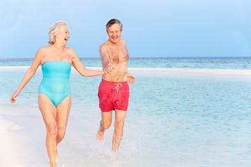 Senior Couple Splashing In Beautiful Tropical Sea