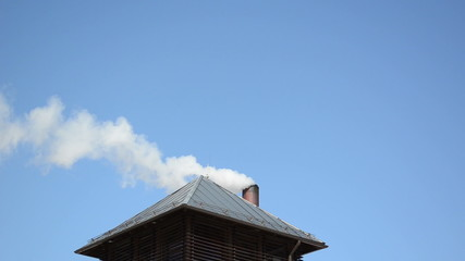 white smoke vapour rise house roof chimney background blue sky