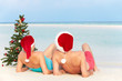 Senior Couple Sitting On Beach With Christmas Tree And Hats