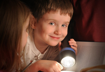 Boy Reading Book at Night with Flashlight