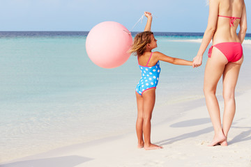 Mother And Daughter Running On Beautiful Beach With Balloon