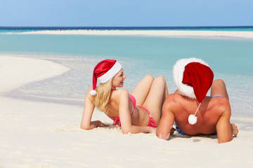 Couple Sitting On Beach Wearing Santa Hats